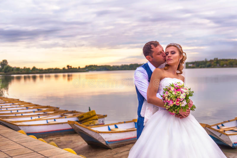 Bride and groom wedding in pier with boats on lake stock photo