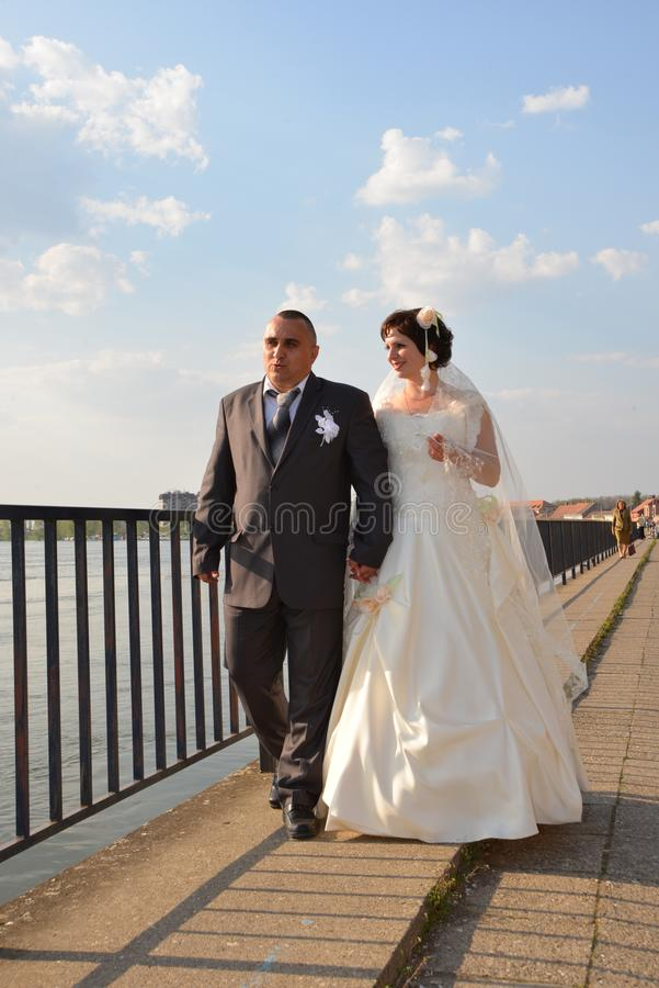 The bride and groom in a white dress walk along the embankment of the river in sunny weather and talk about the future royalty free stock photos
