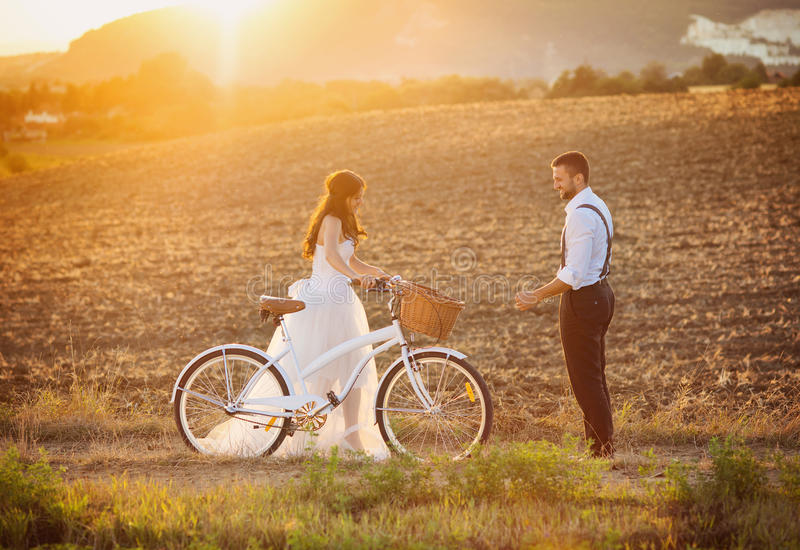 Bride and groom with a white wedding bike stock photography