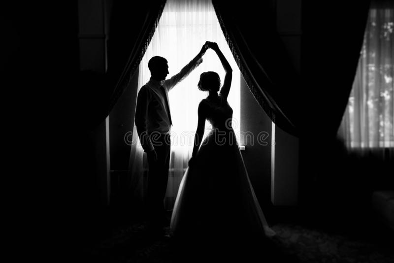 Bride and groom at the window. Silhouette of the bride and groom at the window. Silhouette of newlyweds. Newlyweds at the window. stock photos