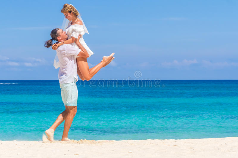 Bride and groom, young loving couple, on their wedding day, outdoor beach wedding on tropical beach and sea background royalty free stock image
