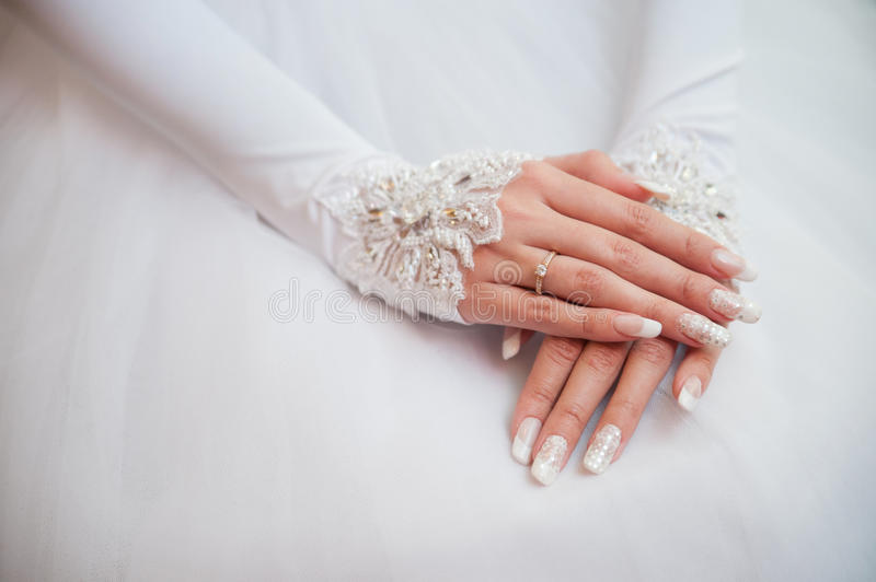 Bride hand with ring. Bride's hand with a ring on her wedding dress stock photography