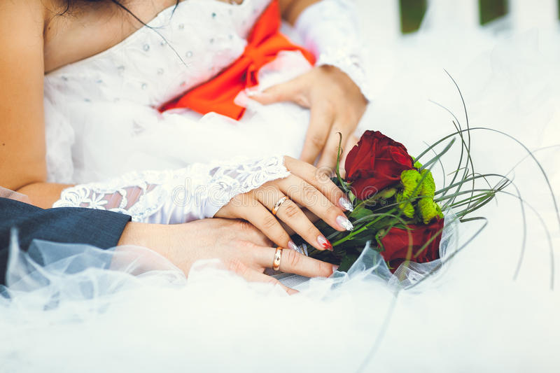 Bride hands with ring and wedding bouquet of flowers. Bride hand with ring and wedding bouquet of red flowers royalty free stock image