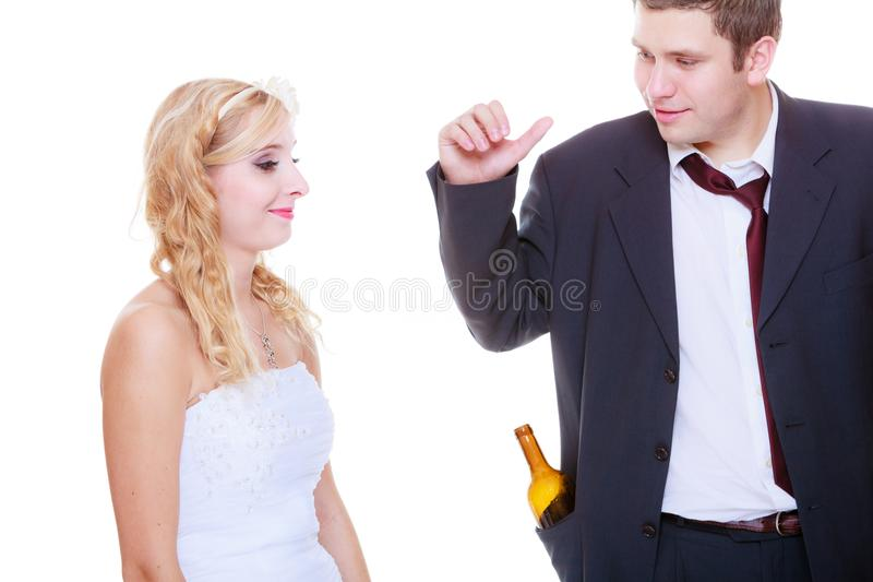 Bride having argument with drunk alcoholic groom. Addiction in relationship, marriage problems and troubles concept. Bride having argument with drunk alcoholic stock photos