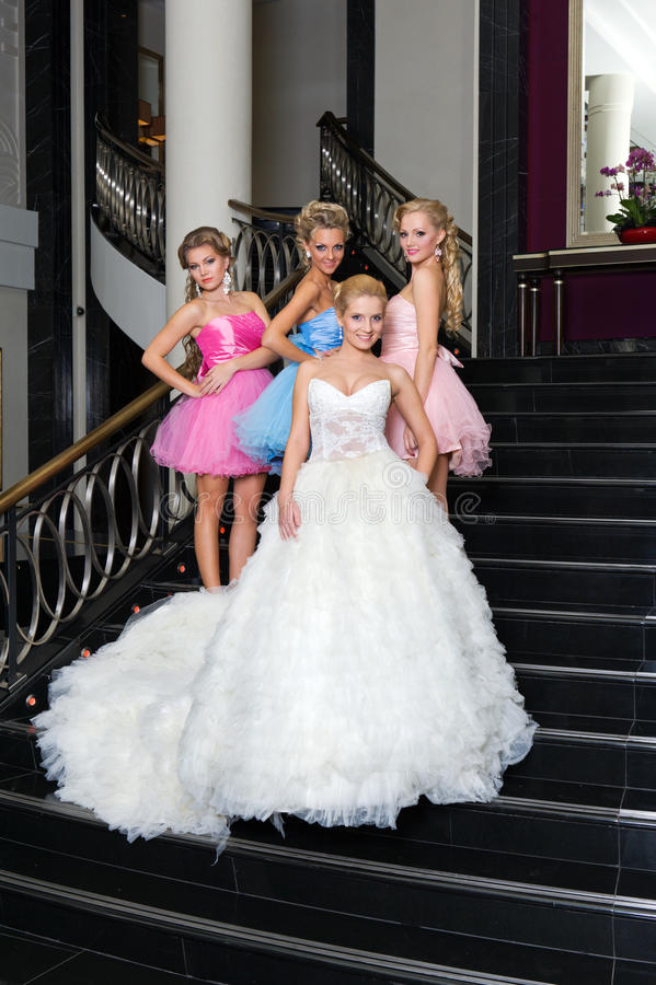 The bride with her bridesmaids on the stairs royalty free stock photography