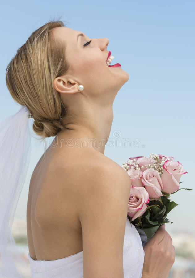 Bride With Her Head Back Holding Flower Bouquet Against Sky. Side view of happy young bride with her head back holding flower bouquet against sky stock photo