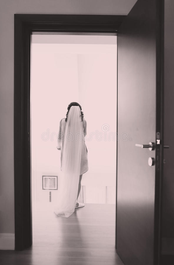 Bride in her room. Young bride dressed in her white wedding gown royalty free stock photos