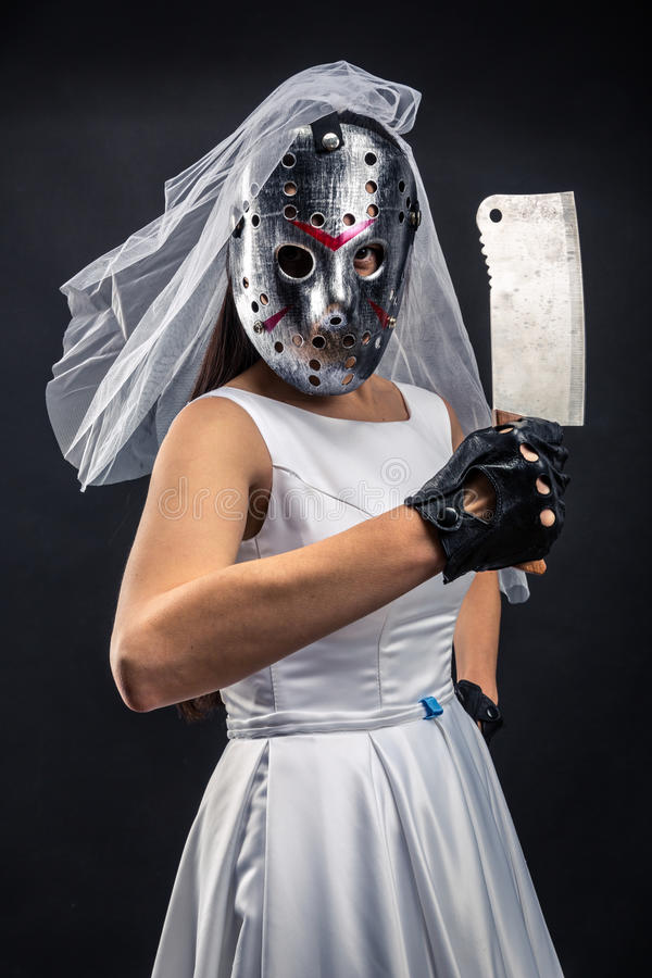 Bride in hockey mask with meat cleaver. Serial murederer in wedding dress royalty free stock images