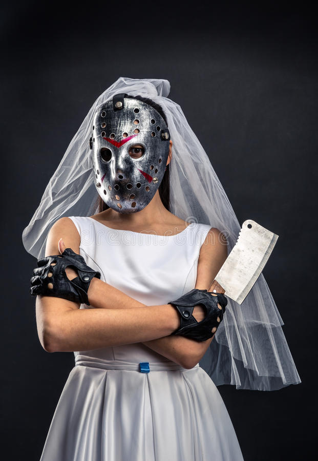 Bride in hockey mask with meat cleaver. Serial murederer in wedding dress stock photography