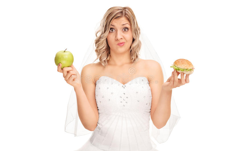Bride holding an apple and a hamburger. Young bride holding an apple in one hand and a hamburger in the other isolated on white background stock photo