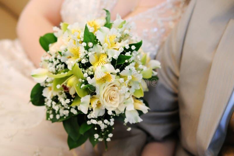 Bride holding beautiful yellow wedding bouquet royalty free stock photo