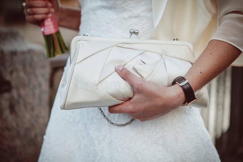 Bride holding bouquet and handbag stock image