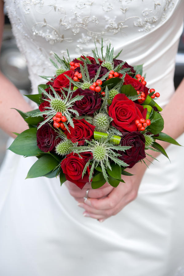 Bride holding a bouquet of roses stock photography