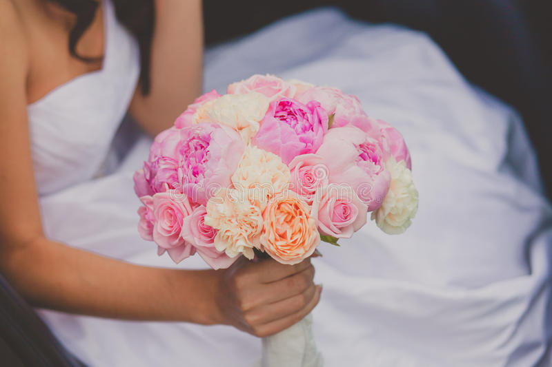 Bride holding bright wedding peony bouquet royalty free stock photography