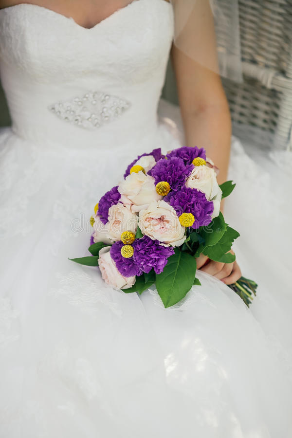 Bride holding delicate marriage bouquet stock photography