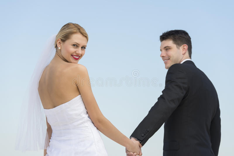 Download Bride Holding Groom's Hand Against Clear Blue Sky Stock Image - Image of looking, newlywed: 32429765