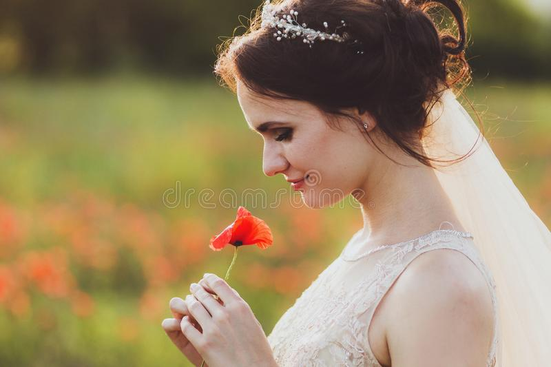 Bride holding in hands poppy flower. And smile royalty free stock photography