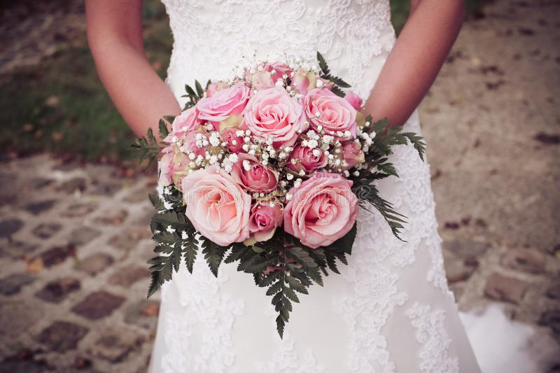 A bride holding her bouquet of roses stock photo