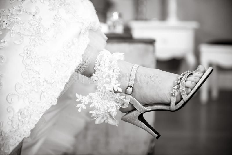 Bride holding her lacy garter on her leg. Black and white photo Close up of bride sliver high heeled shoes and holding her white lace garter royalty free stock photos