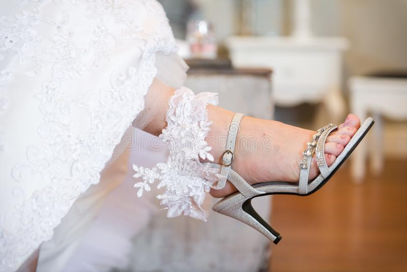Bride holding her lacy garter on her leg stock photography
