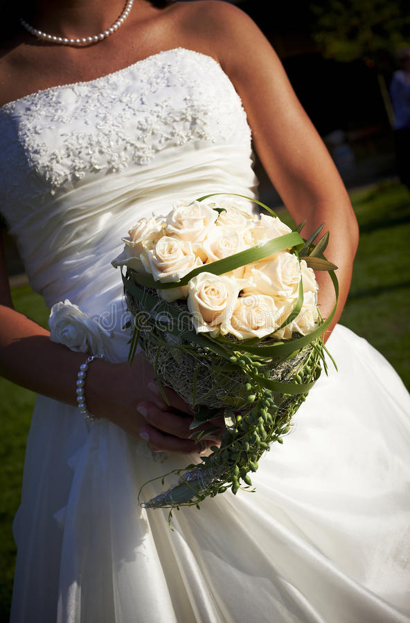 Bride holding rose bouquet. Beautiful lybian bride dressed in white satin holding her flower bouquet with roses in their hands, bodypart stock photo