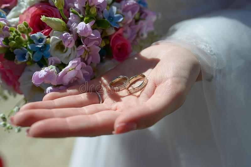 Bride holding a summer mixed flowers bouquet and in the other the wedding rings for him and her stock image