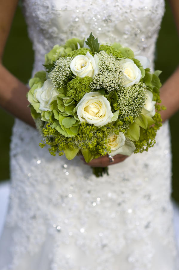 Bride holding a wedding bouquet royalty free stock photography