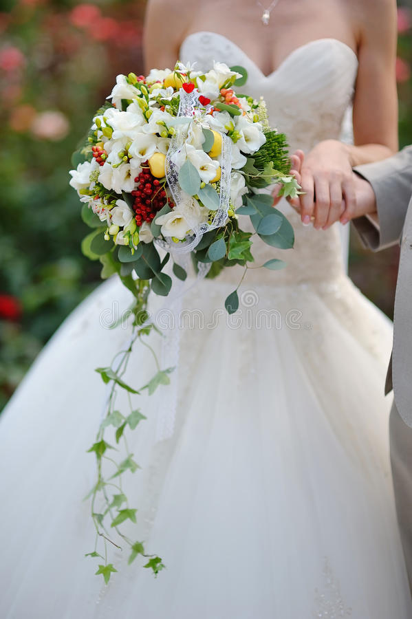 Bride holding wedding bouquet of colorful flowers and roses stock image