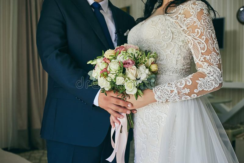Bride holding a wedding bouquet in the hands standing near groom royalty free stock photos