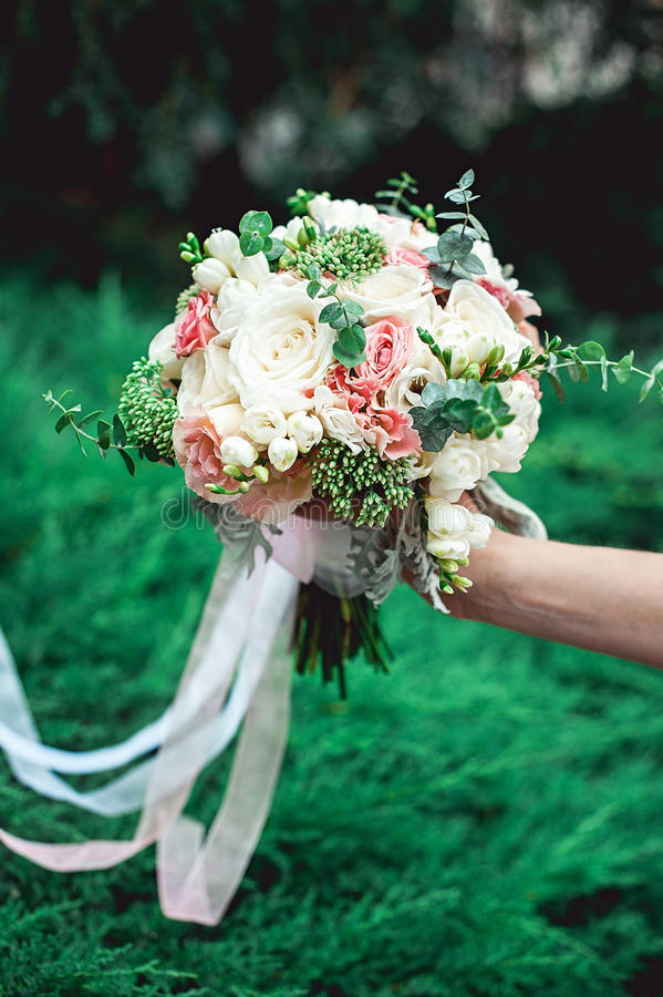 Bride holding a wedding bouquet made of roses royalty free stock photo