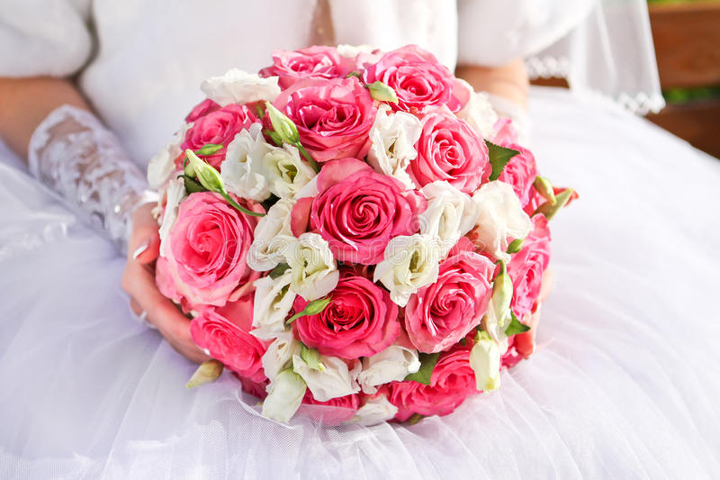 Bride holding a wedding bouquet of roses stock photography