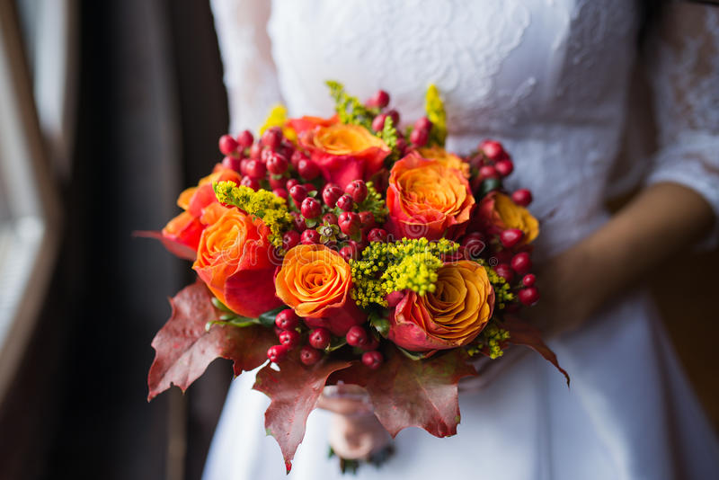 Bride holding wedding Colorful bouquet of autumn flowers royalty free stock image