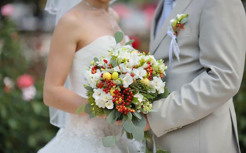 Bride holding wedding flower bouquet of white roses stock image