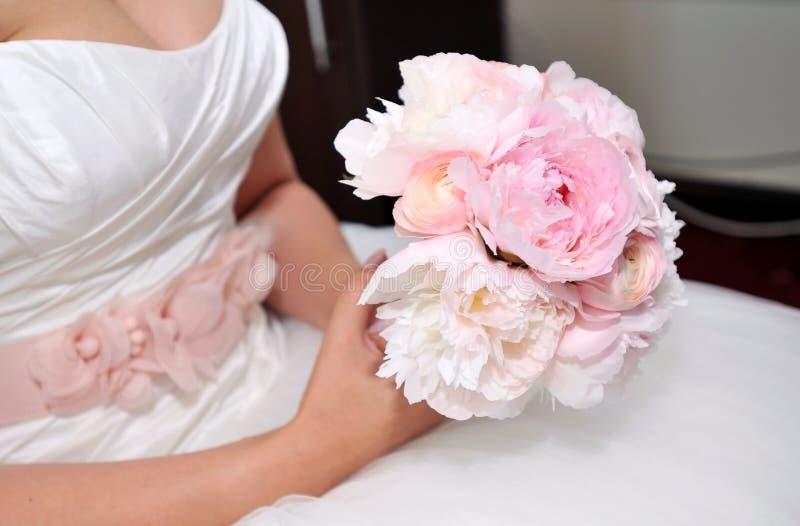 Bride holding wedding flowers stock photo