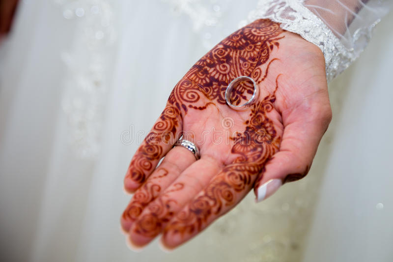 Bride holding wedding ring stock photography