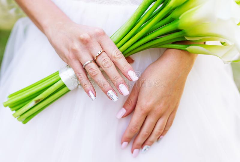 Bride holding white calla lily wedding bouquet stock images