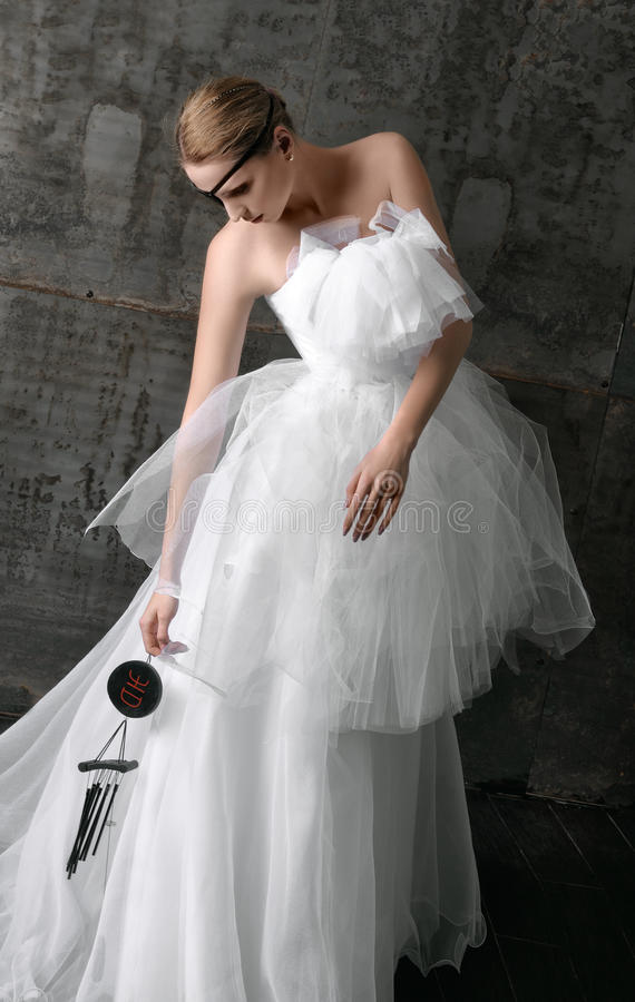 Bride holding a wind chime. Concept: wedding fashion. Bride holding a wind chime. She is wearing a long white dress with a black patch over her eye royalty free stock image