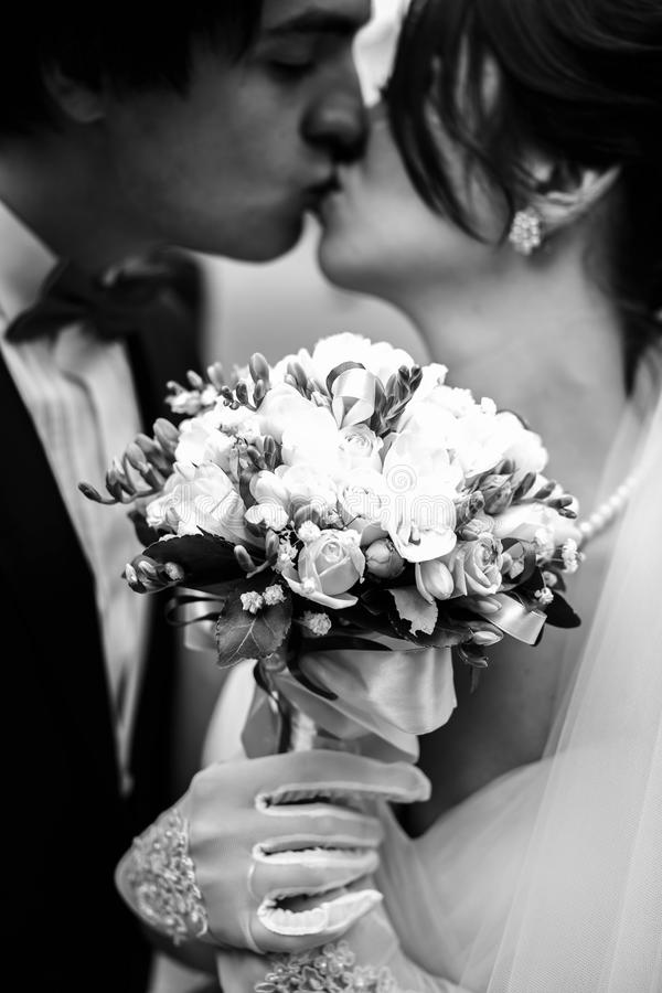 Bride holds a bouquet in hands in white gloves while groom kiss stock photo