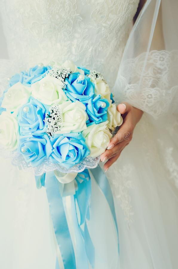 The bride holds a bouquet of roses. Fragment of a white wedding dress. Close-up royalty free stock images