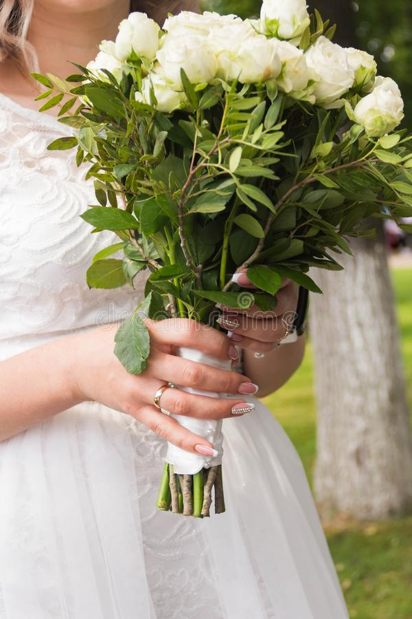 Bride holds a bouquet with white roses. On her finger a wedding ring royalty free stock photos