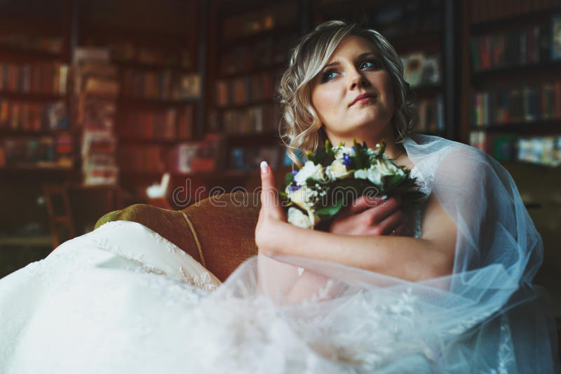 Bride holds her bouquet sitting thoughtful in an old big chair. In the library a stock photo