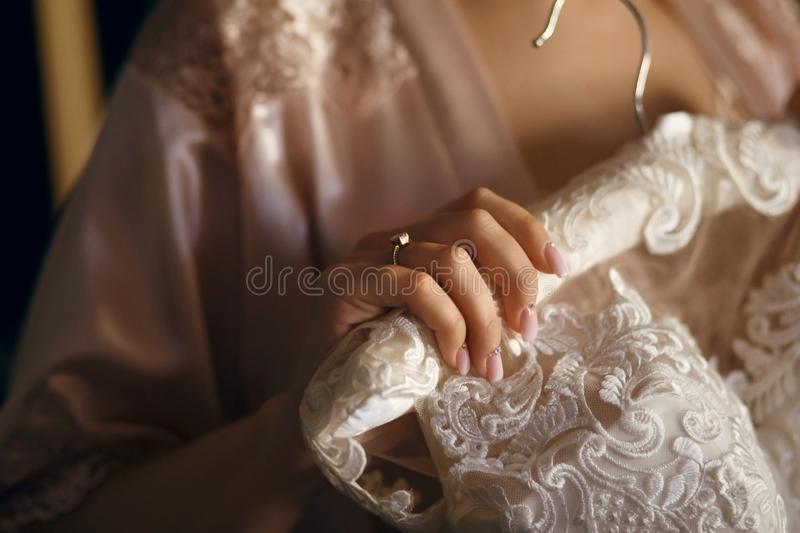 The bride holds in her hand a white dress, on her finger is a wedding ring, the dress hangs on a hanger.  stock photography