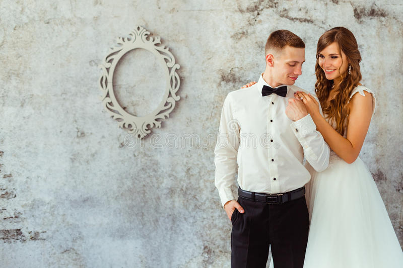 Bride holds her hands on groom& x27;s shoulders. While standing before old grey wall stock image