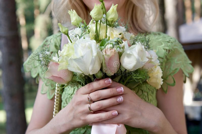 Bride holds in her hands a wedding bouque. T of white and pink roses tied with a pink ribbon royalty free stock images