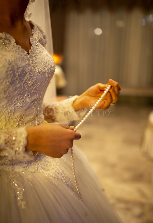 Bride holds in his hands a necklace. Bride holds in hand a beautiful necklace with diamond. Bride holds in his hands a necklace. Bride holds in hand a beautiful royalty free stock image