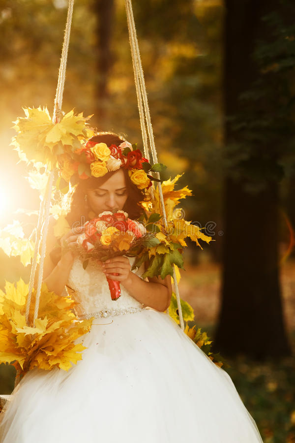 Bride holds a red wedding bouqet in her arms sitting on the swing illuminated with autumn sun royalty free stock images