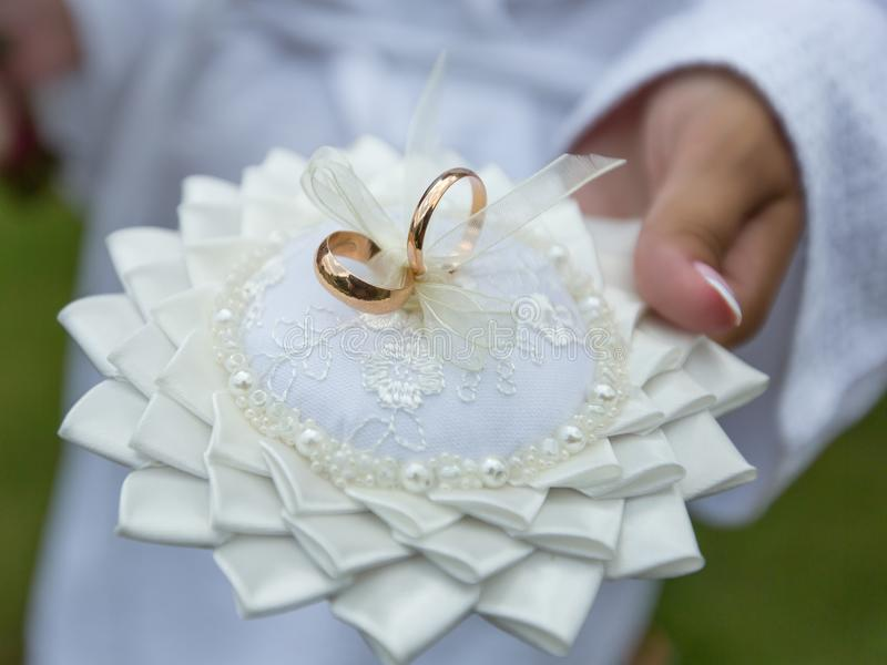 Bride Holds Ring Pillow With Pair Golden Wedding Rings Stock Photo