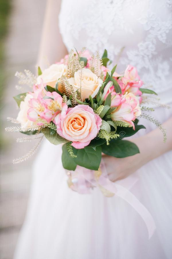 The bride holds a tender bouquet. The bride holds a delicate wedding bouquet of roses, alstromeria, talei and salala stock image
