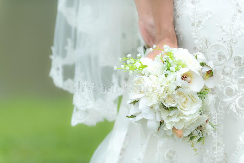 Bride holds a wedding bouquet. Bride wedding white dress in the garden. Nature Background royalty free stock image