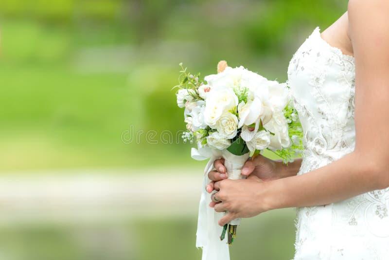 Bride holds a wedding bouquet. Bride wedding white dress in the garden. Nature Background stock photos